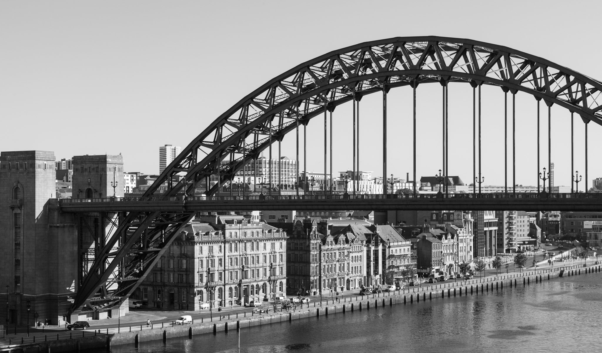 The Tyne bridge crosses from Gateshead into Newcastle on Tyne, spanning the mighty Tyne river and dwarfing the buildings below it on the quayside.