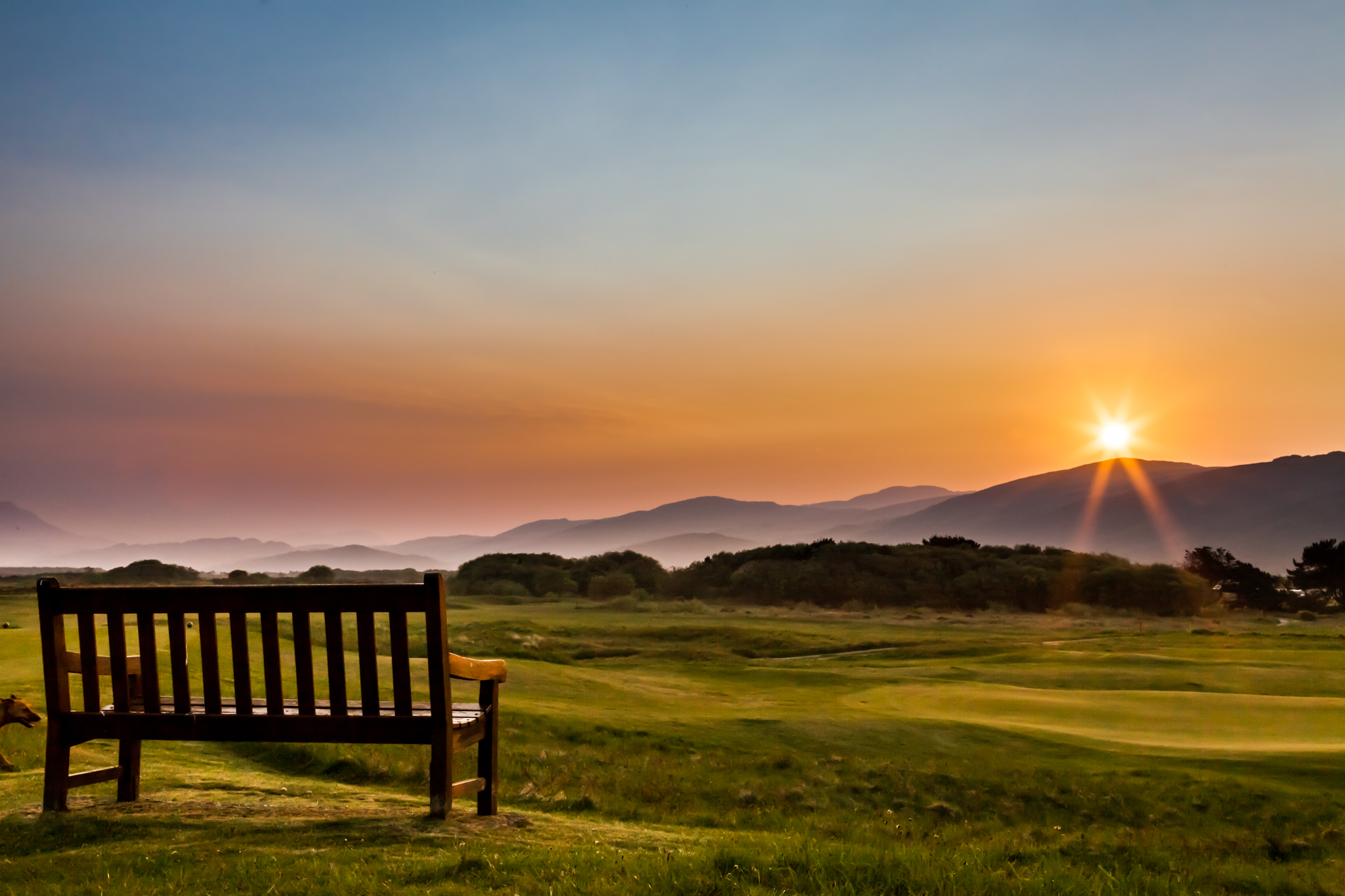 Between Harlech village and teh beach is Harlech golf club. One of their benches has this awesome view on a summers morning, as the sun rises over the Snowdonia mountains.