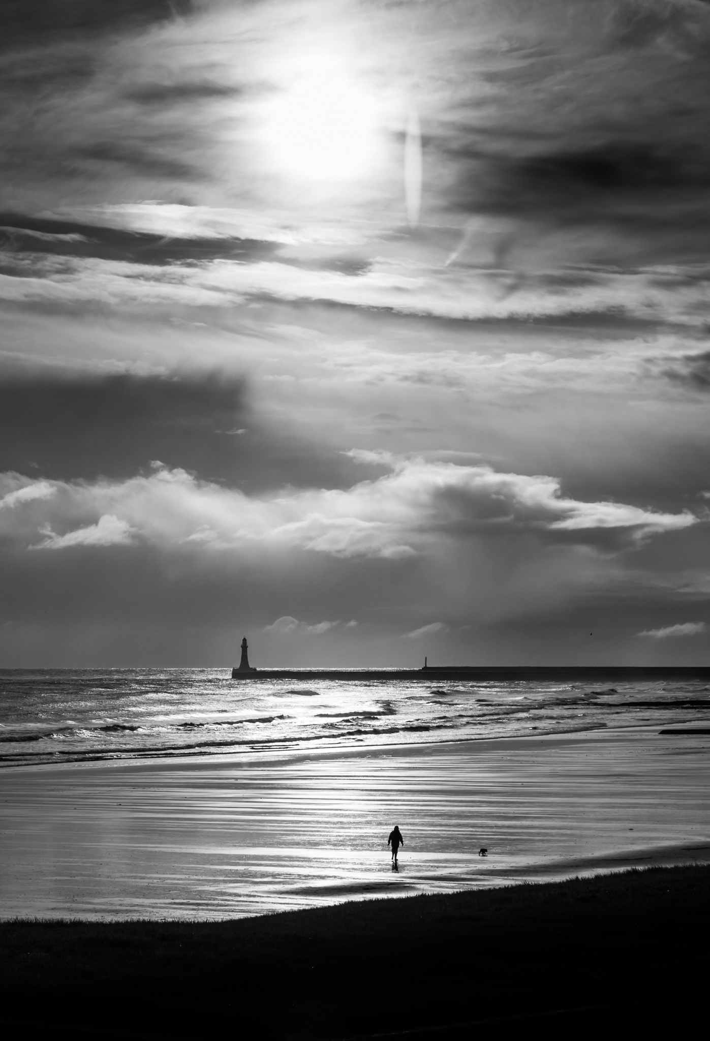 A solitary dog walker on Seaburn beach in Sunderland. The late morning sun struggles to burn off the cloud.