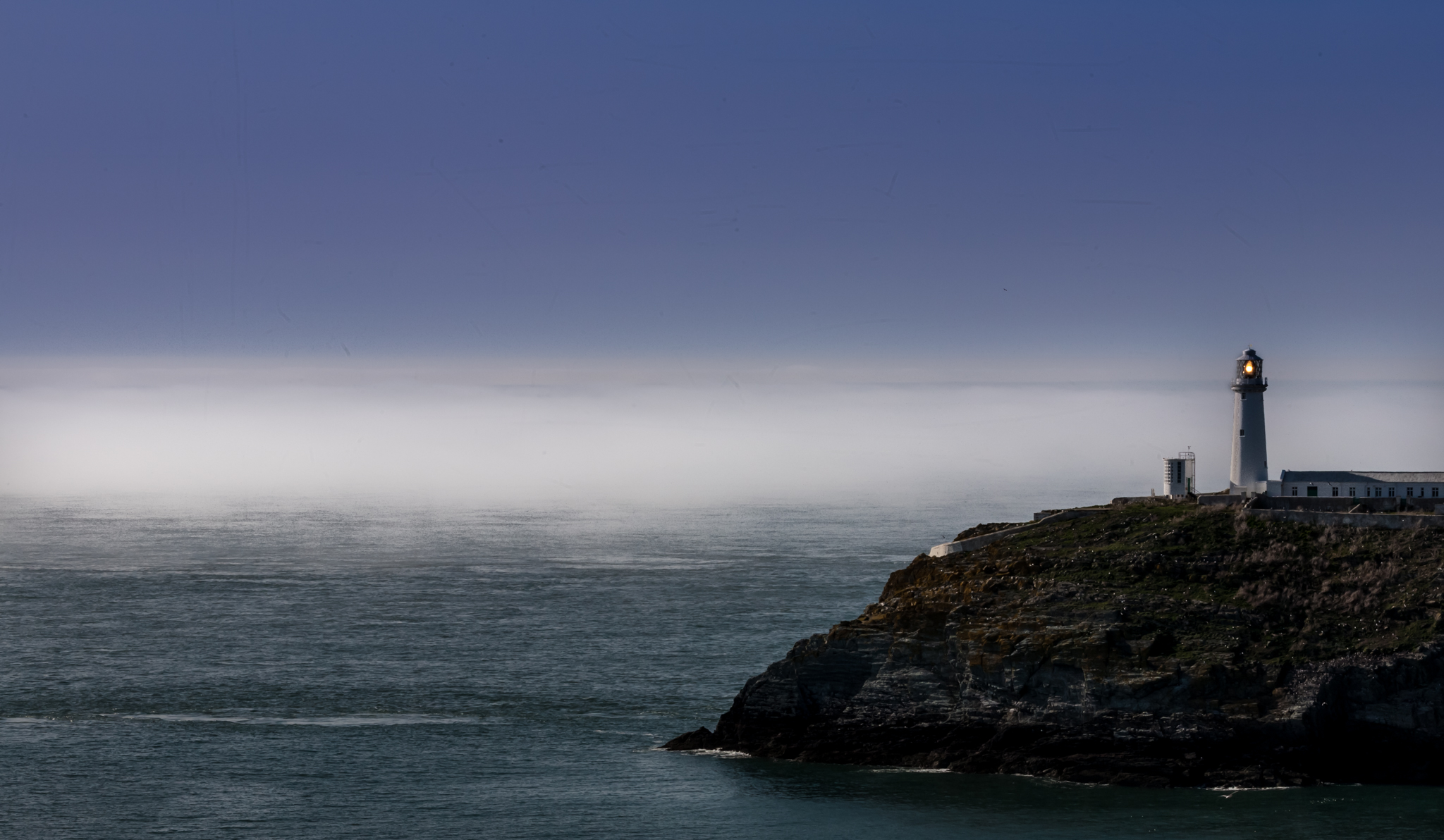 South stack lighthouse shines it's beacon as a thick wall of sea mist rolls in toward the coast, obliterating all visual aids for sailors.