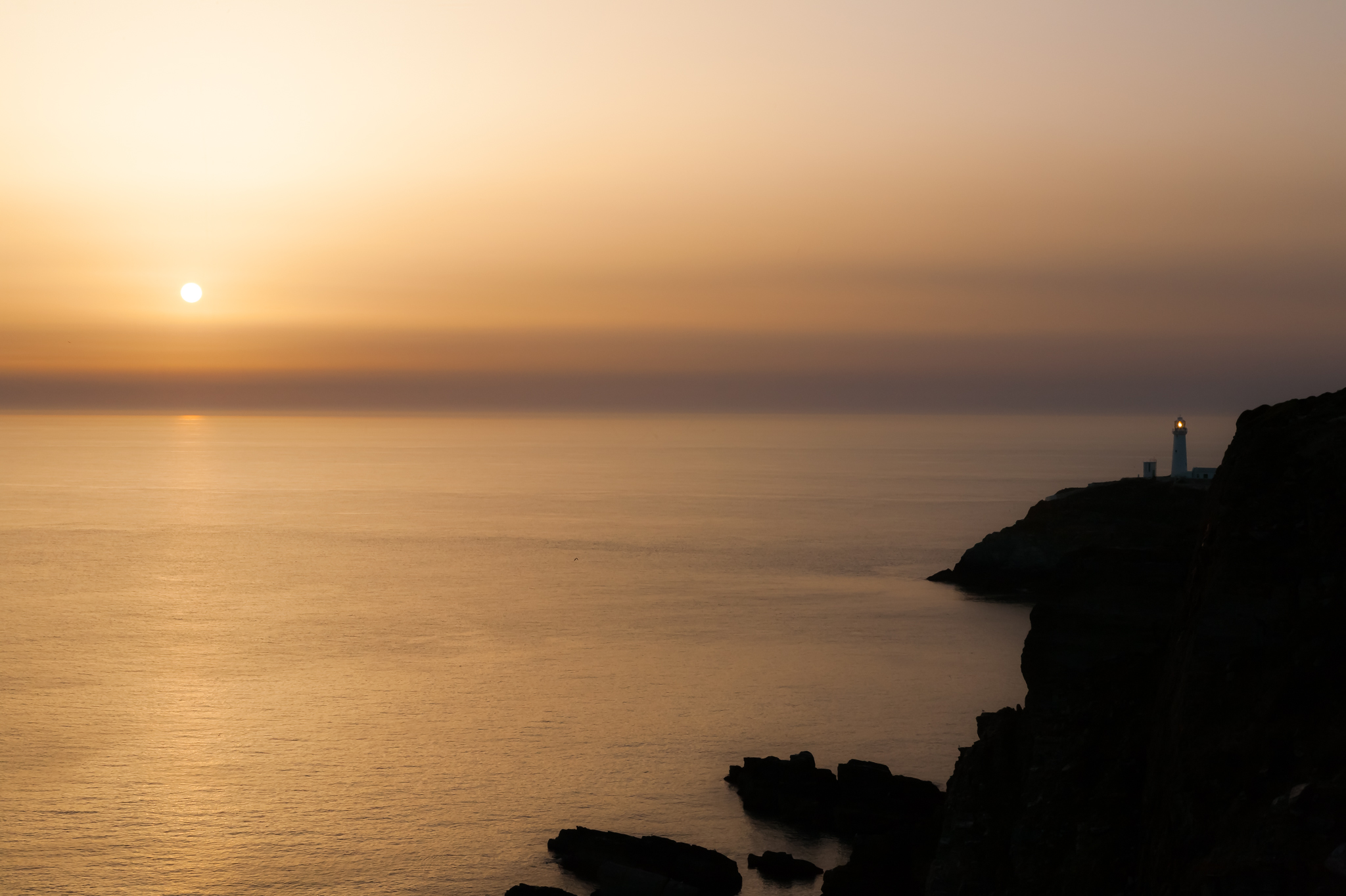 As the sun goes down over the Irish sea off the coast of Angelesey in North Wales,  the lighthouse at South Stack comes on, warning shipping if nearby hazards. The quality of this light attracted me into taking the shot.
