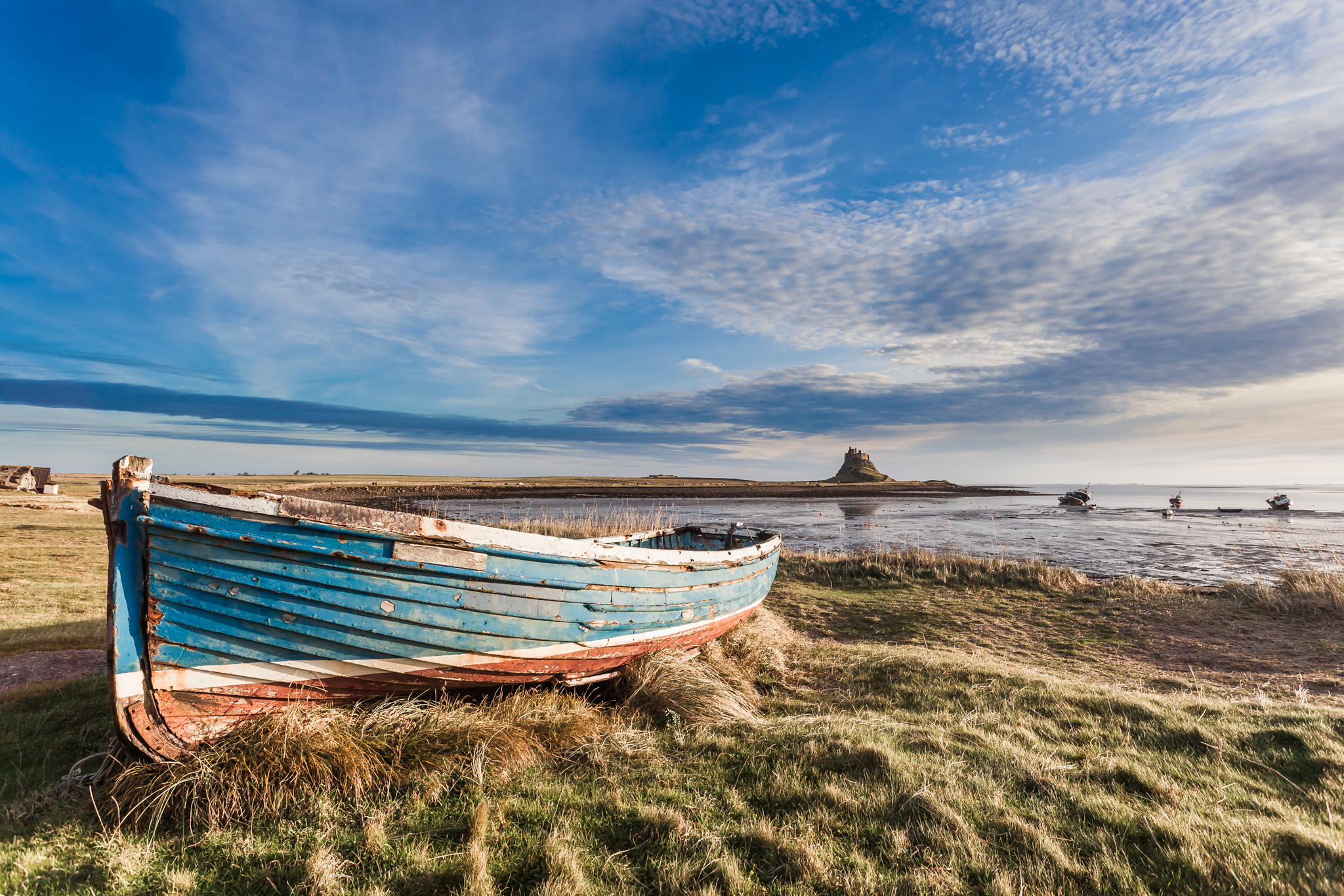 Another derelict boat sits on the shore of  the Holy Island of Lindisfarne in Northumberland, with the castle in the distance.