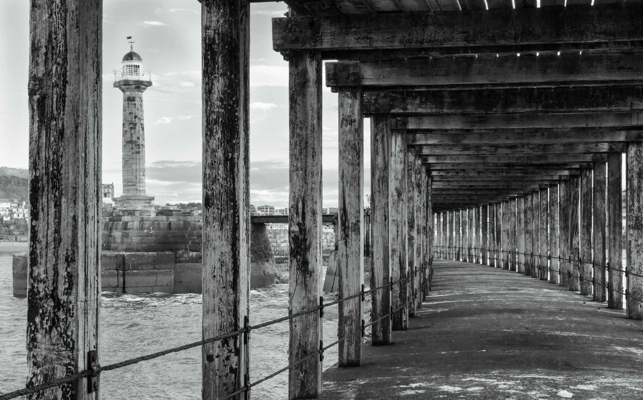This monochrome image is a view from the lower level of the harbour wall at Whitby, North Yorkshire. The disused lighthouse can also be seen between the wood pillars.