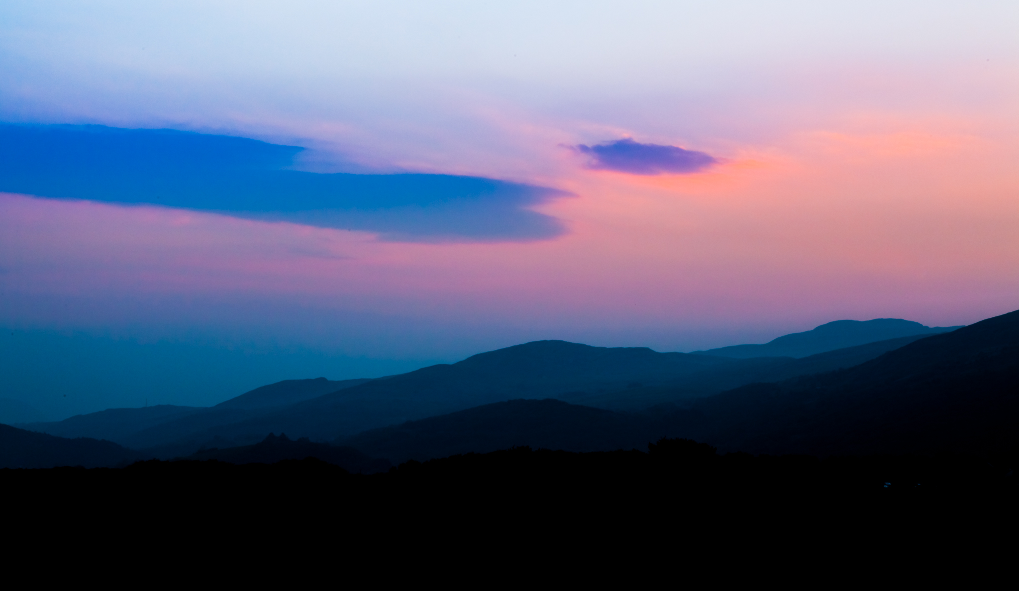 The sun slowly rises toward the hills behind Harlech, north Wales.