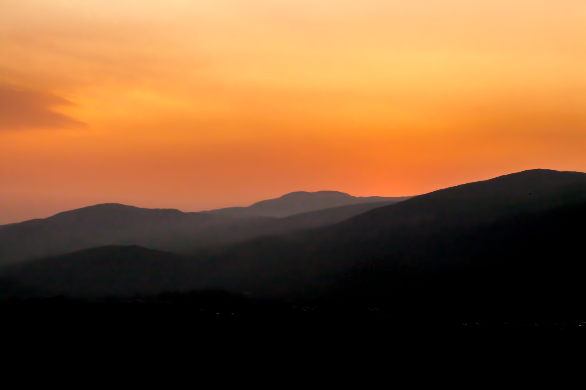 Another sunrise, a warm red and orange sunrise, lights up the mountains behind Harlech in north Wales.