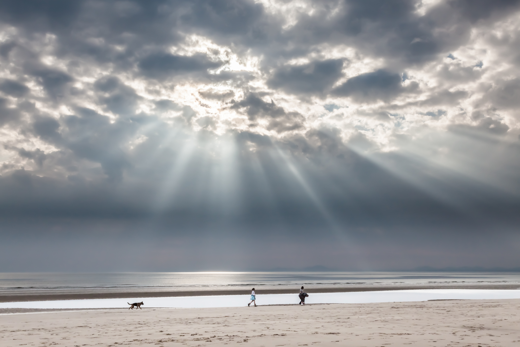 A couple out walking on Harlech beach, with their daughter and dog, seem oblivious to the amazing sunbeams coming through the clouds to illuminate the beach and the sea.