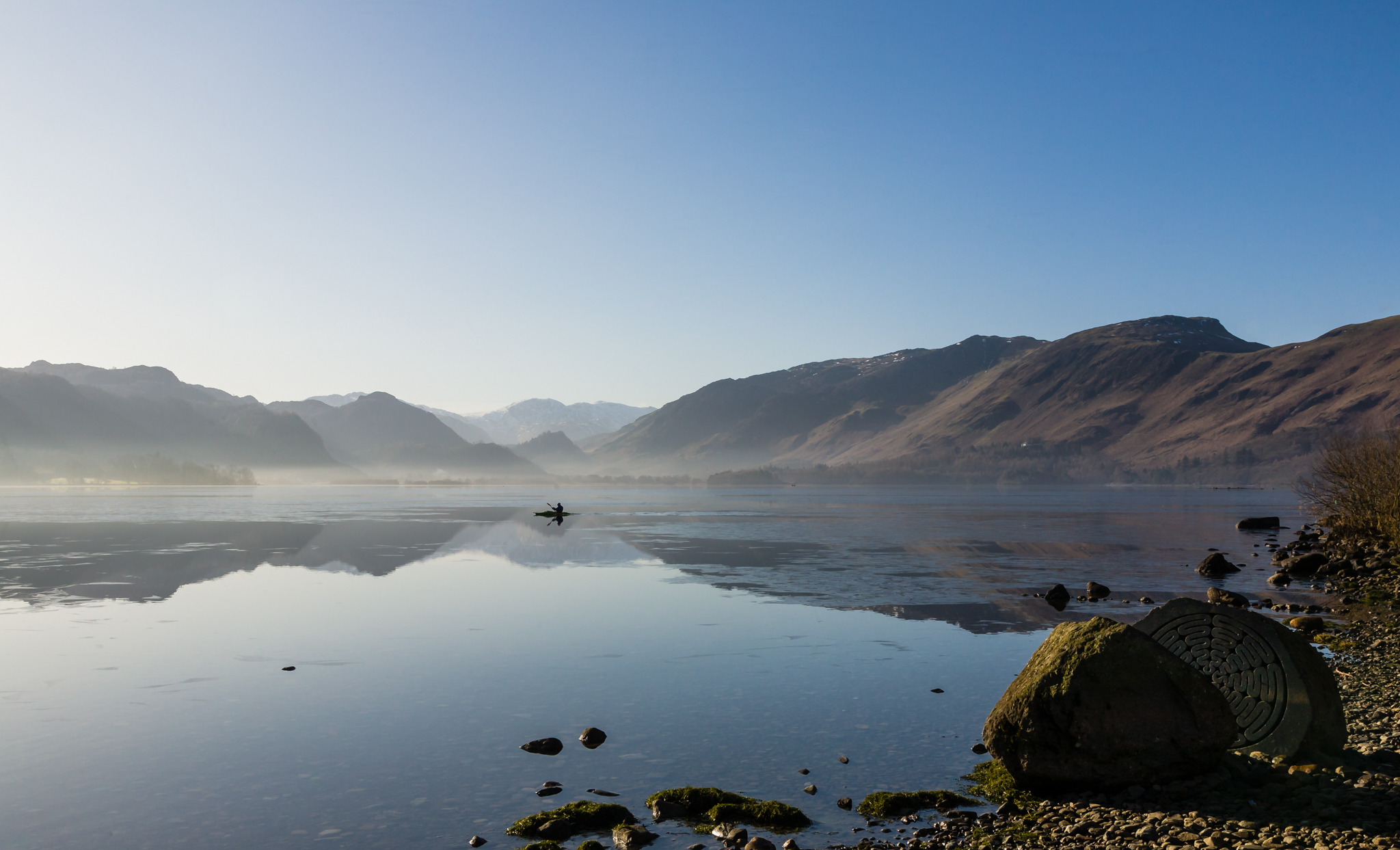 A man braves the early morning winters cold to canoe through the ice on Cumbria's Derwent Water near Keswick.