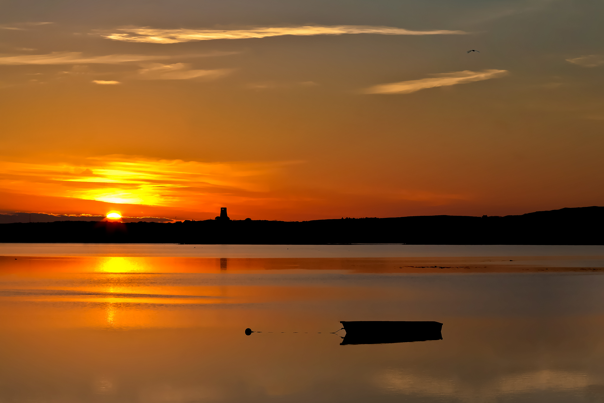 The sun goes down over a moored rowing boat at Holyhead, Isle of Anglesey, north Wales.