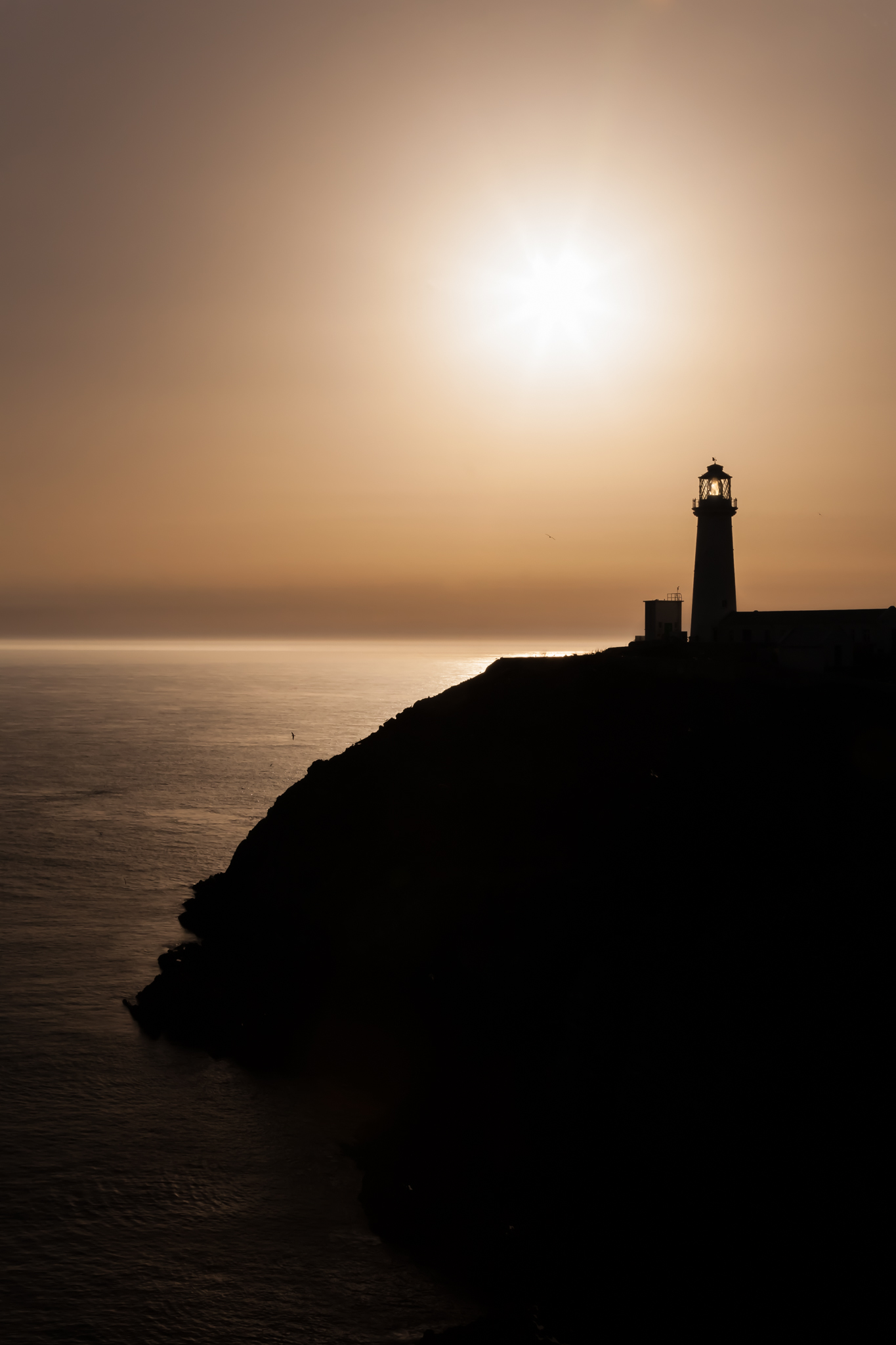 The sun goes down off Anglesey in North Wales, silhouetting South Stack lighthouse against the horizon.